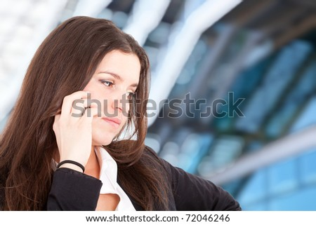 Young businesswoman talking at phone. Blurred background. - stock photo