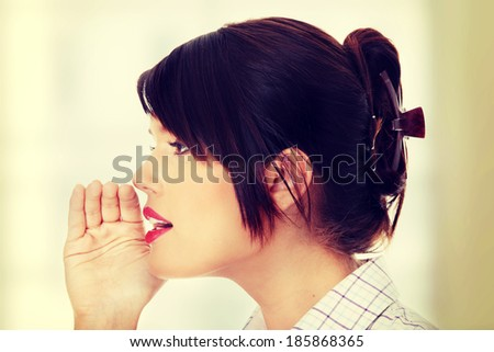 Young businesswoman talking gossip - stock photo