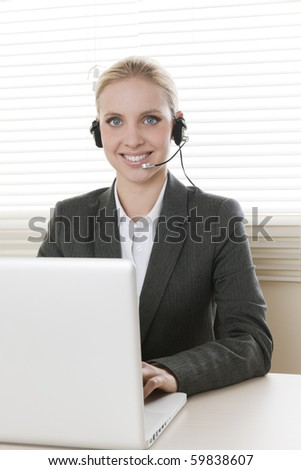 Young businesswoman talking on headset - stock photo