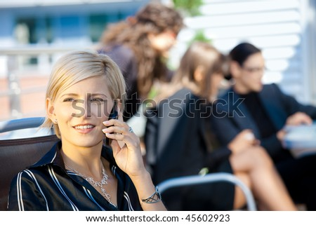 Young businesswoman talking on mobile phone, outside office building. - stock photo