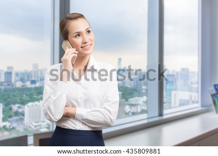 Young businesswoman talking on mobile phone while standing by window in office. - stock photo