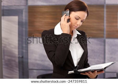 Young businesswoman talking on mobilephone, looking at personal organizer. - stock photo