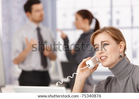 Young businesswoman talking on phone in office, colleagues chatting in background.? - stock photo