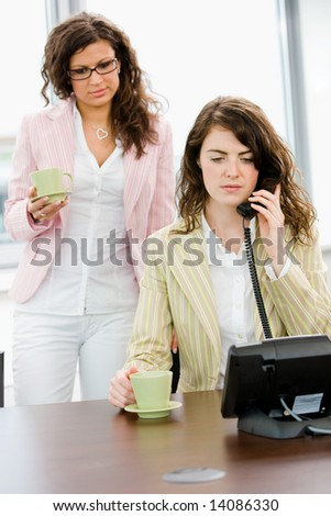 Young businesswoman talking on phone while coworker holding coffee cup. - stock photo