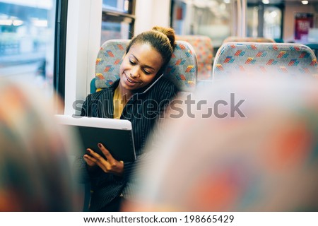 Young businesswoman talking on the phone and using tablet computer on train - stock photo