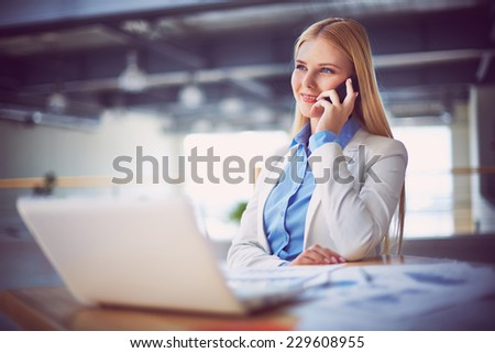Young businesswoman talking on the phone during break - stock photo