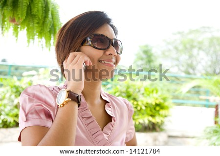 Young businesswoman talking on the phone in a relaxed home environment - stock photo