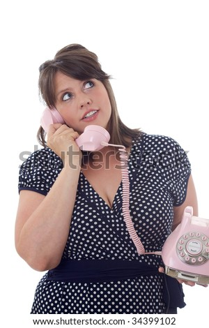 Young businesswoman talks on a pink landline telephone; isolated on a white background. - stock photo