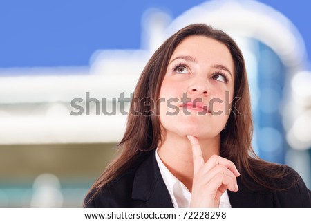 Young businesswoman thinking something. Out of focus construction and blue sky in the background. - stock photo