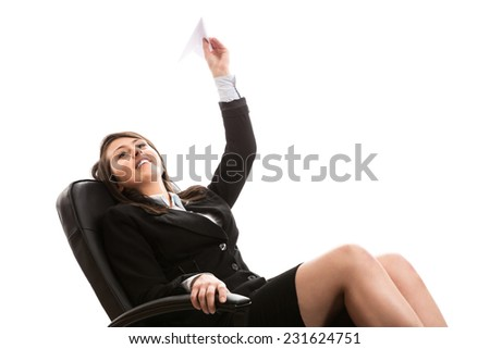 Young businesswoman throwing a paper plane - stock photo