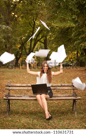 Young businesswoman throwing paper in the air - stock photo