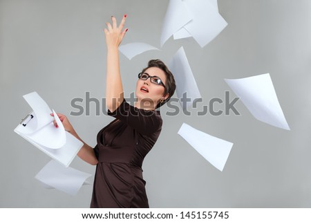 Young businesswoman throws paper document pages against light gray background - stock photo