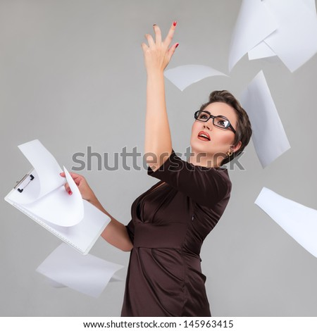 Young businesswoman throws paper document pages against light gray background