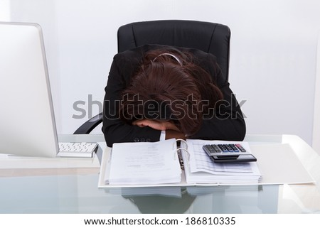 Young businesswoman tired of calculating tax at desk in office - stock photo