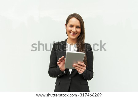 Young businesswoman touching tablet by the wall in the city. - stock photo