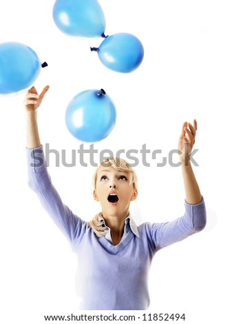 Young businesswoman trying to catch the balloons - stock photo