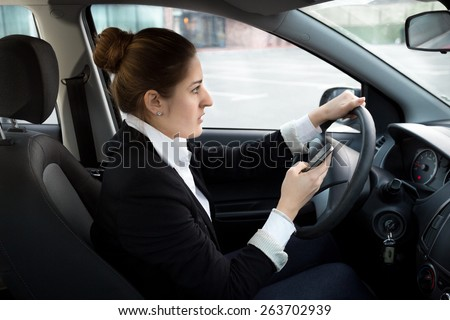 Young businesswoman typing message while driving a car