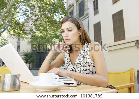 Young businesswoman using a laptop computer while sitting in a coffee shop in the city, outdoors. - stock photo