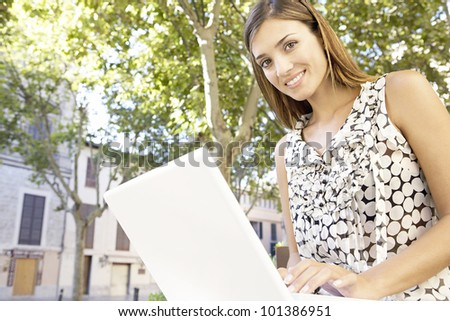 Young businesswoman using a laptop computer while sitting on a bench in the city. - stock photo