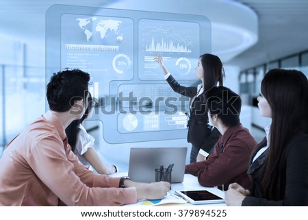 Young businesswoman using a virtual screen to deliver a presentation and explaining business solutions - stock photo