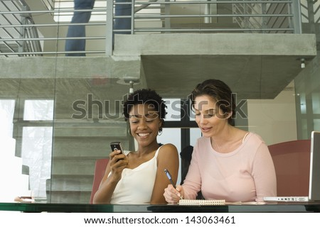 Young businesswoman using cellphone with female colleague noting down on notepad in office - stock photo