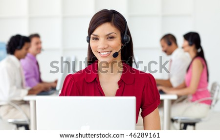 Young Businesswoman using headset in a call center - stock photo