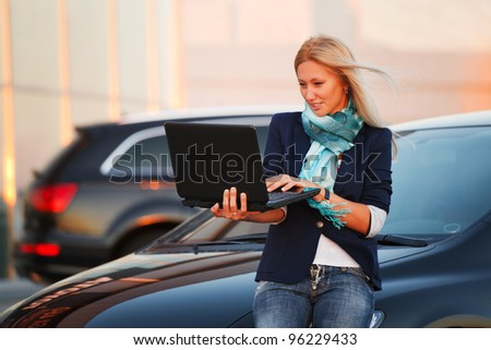 Young businesswoman using laptop against office windows - stock photo