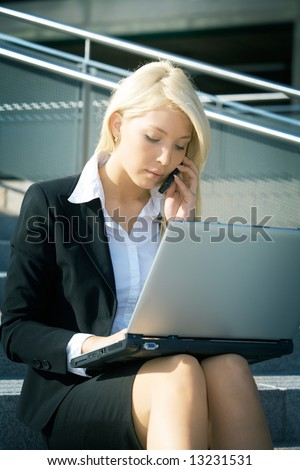 Young businesswoman using laptop computer in city, sitting on stairway - stock photo
