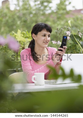 Young businesswoman using mobile phone at table - stock photo