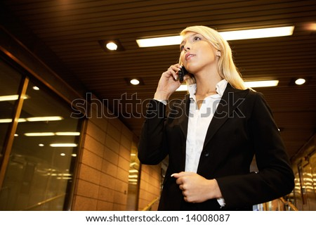 Young businesswoman using mobile phone in passageway of office building - stock photo
