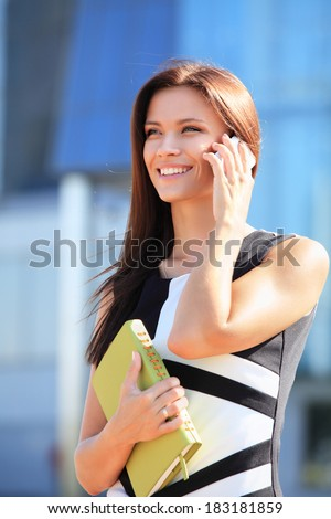 young businesswoman using mobile phone or smartphone over building background - stock photo