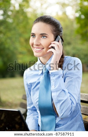 young businesswoman using phone in park - stock photo