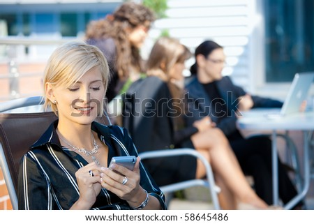 Young businesswoman using smart mobile phone, outside office building. - stock photo