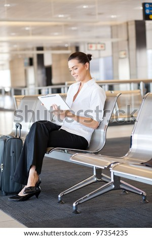 young businesswoman using tablet computer at airport - stock photo