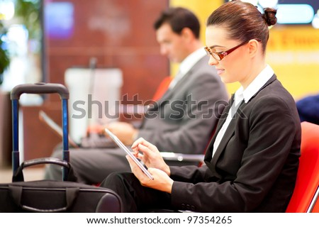 young businesswoman using tablet computer at airport while waiting for her flight - stock photo