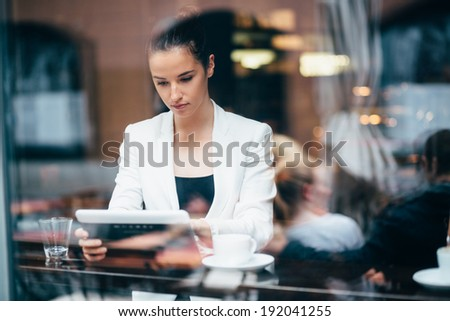 Young businesswoman using tablet computer in coffee shop - stock photo