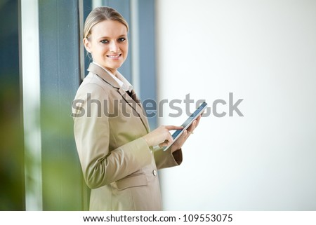 young businesswoman using tablet computer in office - stock photo