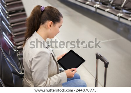 Young businesswoman using tablet computer while waiting for flight at airport lobby - stock photo