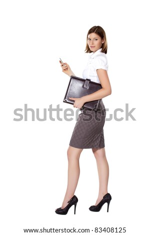 Young businesswoman walking and using phone and holding a leather folder - stock photo
