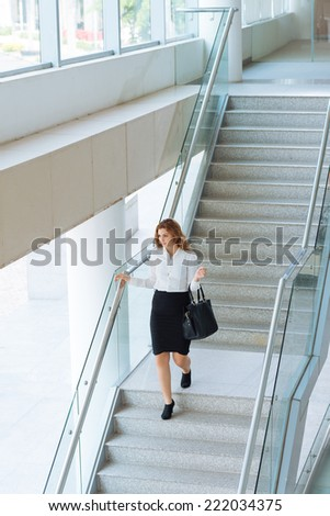 Young businesswoman walking downstairs in office building  - stock photo