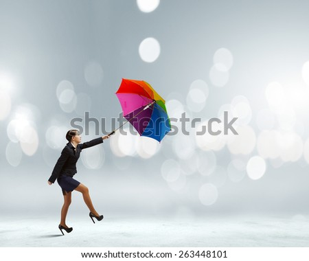 Young businesswoman walking on roof with colorful umbrella - stock photo