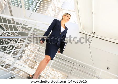 young businesswoman walking on stairs - stock photo