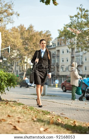 young  businesswoman walking on street in urban city - stock photo