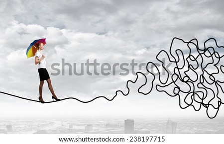 Young businesswoman walking on twisted rope high in sky - stock photo