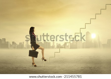 Young businesswoman walking up on stairs for success - stock photo