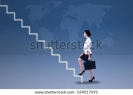 Young businesswoman walking up on stairs with world map background - stock photo