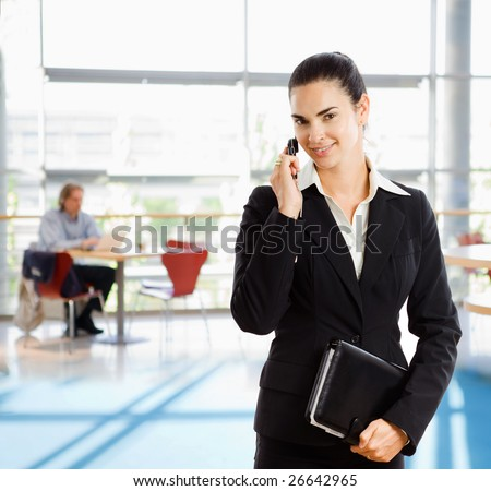 Young businesswoman wearing black suit, holding personal organizer talking on mobile phone in office building lobby.