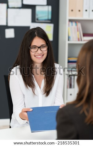Young businesswoman wearing glasses in a job interview handing over a file with her curriculum vitae to the interviewer with a a smile - stock photo