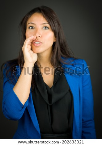 Young businesswoman whispering message with cupping hands over mouth - stock photo