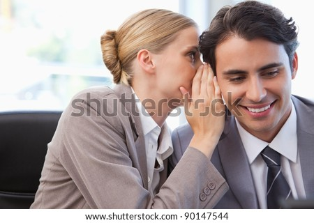 Young businesswoman whispering something to her colleague in a meeting room - stock photo